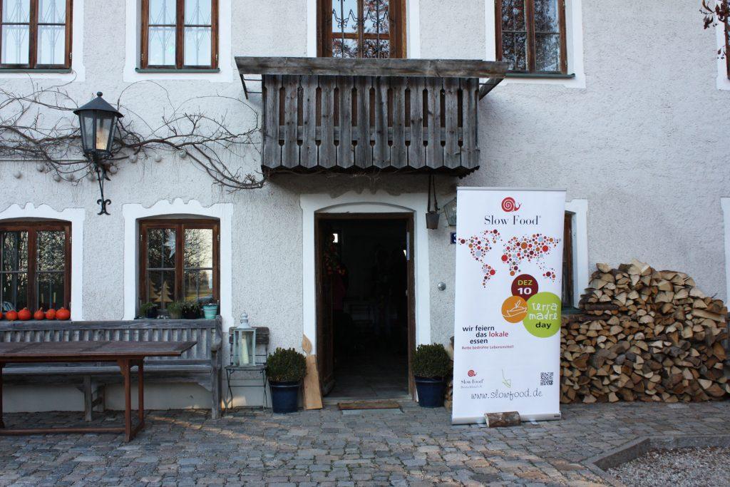 Eingang zum Bauernhaus von Julia Reimann und Stefan Schmutz im Chiemgau. Vor der Tür steht das Slow Food Plakat